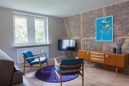 TV, sideboard and two chairs in living room with brick wall