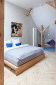 Wooden double bed in attic bedroom