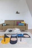 Couchtisch mit Marmorplatte auf bunt gemustertem Teppich vor Polstersofa