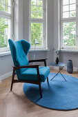 Blue wing-back chair and side table on round rug in window bay