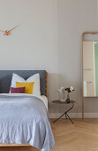 Double bed, bedside table and full-length mirror leaning against wall