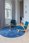 Blaue Sessel und Beistelltisch auf rundem Teppich vor Fenster