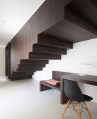 Desk below staircase boxed in with dark wood