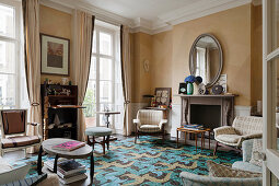 Fireplace, beige silk wallpaper and patterned carpet in living room