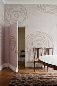 Dusky pink wallpaper with abstract floral pattern in period apartment