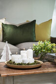 Candles in bed of moss in bamboo dish on coffee table