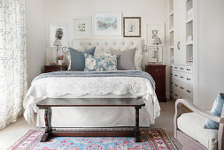 Scatter cushions on double bed in bright bedroom
