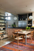 Wooden table and chairs on multicoloured rug in open-plan kitchen