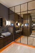 Mirrored fitted cupboards in bathroom in shades of grey