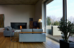 Couch and fireplace in seating area with floor-to-ceiling sliding glass doors leading onto roof terrace