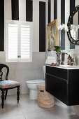 Washstand, toilet and upholstered chair in black-and-white bathroom