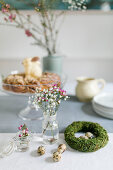 Wreath of moss, quail eggs and spring flowers in jars