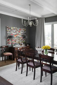 Dining table and chairs in dark wood in dining room with grey walls
