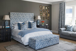 Double bed with upholstered headboard and matching storage bench in bedroom with dark accent wall
