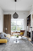 Yellow upholstered sofa, coffee table and classic chair in the living room with gray carpet