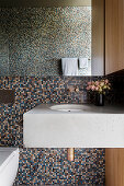 Concrete vanity in front of mosaic tiles in the bathroom