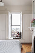 Double bed in front of windowsill as a bench in a white bedroom