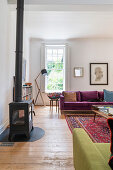 Log-burning stove and sofas in purple velvet and lime-green upholstery in living room