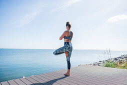 Woman doing yoga (tree pose) next to the sea