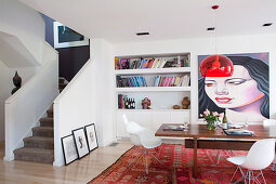 Dining table with shell chairs in front of bookshelf and artwork