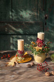 Autumnal arrangement of candles and flowers on plate and in jug