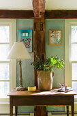 Branches in jug and lamp on old wooden table in front of wooden beam