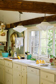 Country-house-style kitchen with wooden beams and lattice window