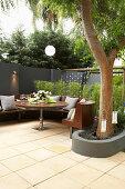 Runde Bank und Tisch auf der Terrasse unterm Baum