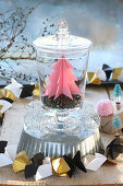 Pink paper Christmas tree in jar on top of cake tin with origami garland