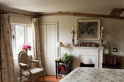 Bedroom with low ceiling and fireplace in English country house