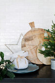 Wooden cutting boards, gifts and Christmas decorations in front of a white tiled wall