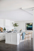 Kitchen island with bar stools in white contemporary kitchen