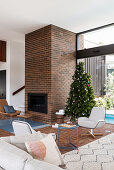 Fireplace in the brick wall in the living room with Christmas tree