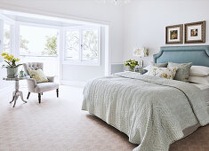 Blue and gray bedroom with bay window to the balcony