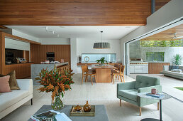 Open living room with sliding glass element to the terrace with outdoor kitchen