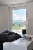 Weiße Ablage mit Designerlampe am Bett mit schwarzer Bettwäsche im Schlafzimmer