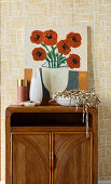 Picture with floral motif and bowl with tinsel on retro cupboard