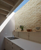 Kitchen counter, brick wall and skylight in modern kitchen