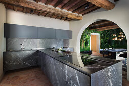 Black marble panels and rustic beams in modern kitchen