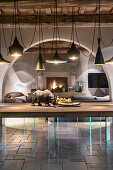 Designer lamps above wooden table on glass legs in rustic country house