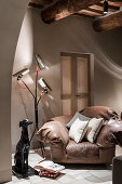 Dog status and designer lamp next to brown leather armchair