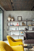 Yellow armchair and minimalist shelving in living room