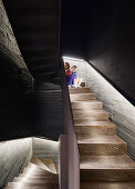 Two children in dark stairwell with board-formed concrete walls