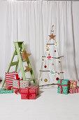 Hängender DIY-Weihnachtsbaum aus Seil und Ästen, verpackte Geschenke und Leiter