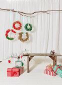 DIY-Weihnachtskränze aus Stoffresten, Holzbank und verpackte Weihnachtsgeschenke