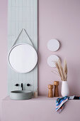 Vanity with countertop basin and round mirror on pastel wall