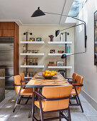 Designer lamp above table and leather chairs in dining area
