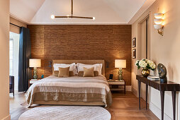 Double bed in bedroom with bamboo wall