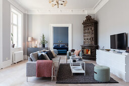 Stucco frieze and antique tiled corner stove in living room of period apartment