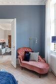 Dusky-pink velvet récamier in corner of bedroom in period apartment